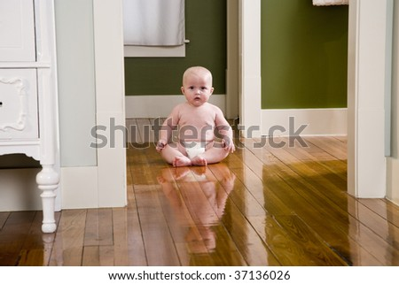Chubby seven month old baby at home sitting on wood floor - stock photo