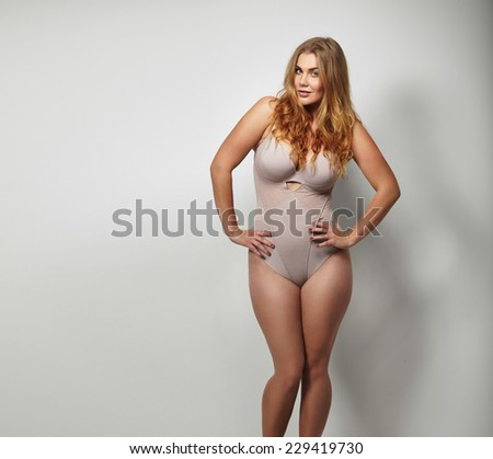 Chubby young woman in body stockings standing on grey background with her hands on hips looking at camera. Caucasian plus size female model in lingerie with copy space. - stock photo