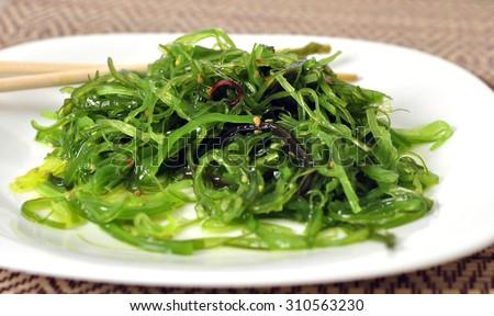 chuka salad of green seaweed with sesame seeds on a bamboo napkin with bamboo sticks - stock photo