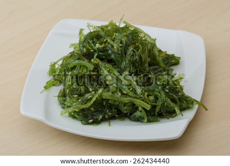 Chuka salad with sesame seeds on the wood background