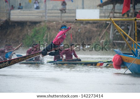 CHUMPHON ,THAILAND-NOV 4 : Unidentified rowers in Climbing Bows toward Snatching a Flag native Thai long boats compete during Native Long Boat Race Championship on Nov 4, 2012 in Chumphon ,Thailand .