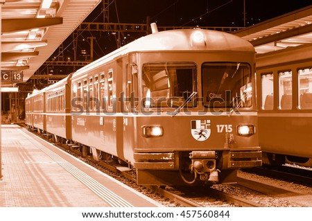 Chur, Switzerland - June 06, 2010: Passenger train stands by the platform at night time. - stock photo