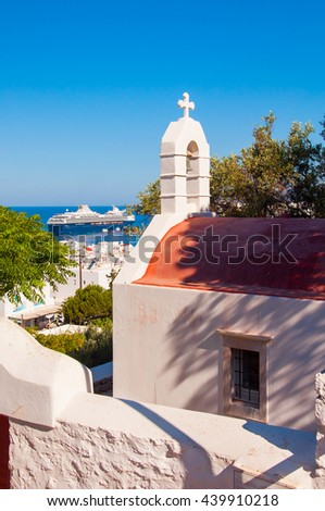 Church above the town of Mykonos and the cruise ship at sea. - stock photo
