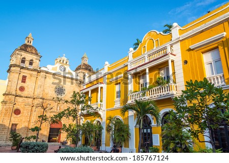 Church and yellow colonial building visible from San Pedro Claver plaza in historic Cartagena, Colombia - stock photo