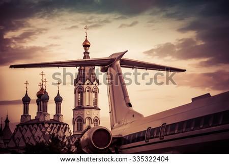 Church behind the passenger aircraft - stock photo