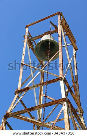 church bell and rusty bell tower and chain in a blue sky background