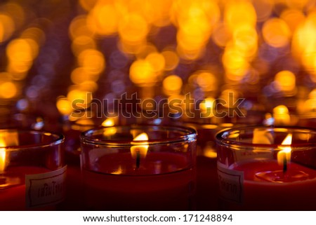 Church candles in red transparent chandeliers - stock photo