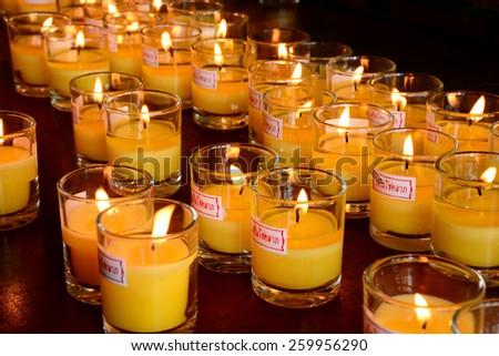 Church candles in yellow transparent chandeliers. - stock photo