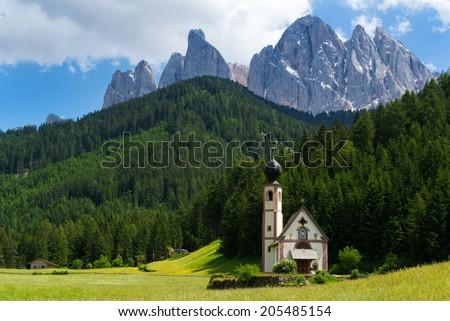 Church in Valle de Funes, Dolomites, with Geislerspitzen in the background - stock photo