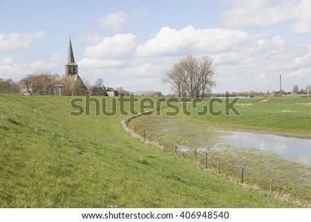 church of ravenswaaij and green grassy meadows near rhine embankment in south holland - stock photo