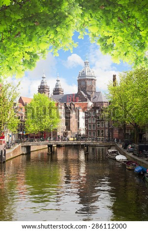 Church of St Nicholas, old town canal with green trees at summer day, Amsterdam, Holland - stock photo