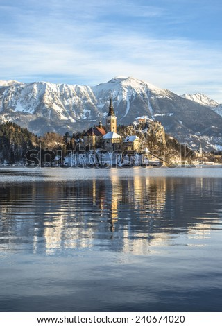 Church on Island and Castle at Bled. Early morning on Bled lake. Scenic and atmospheric sunrise on Bled in Slovenia. Beautiful reflection of the island. Winter fairytale at the alpine village.