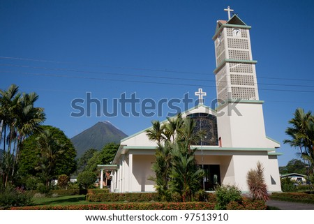 Church on main square of La Fortuna village, Costa Rica, with Arenal Volcano in background - stock photo