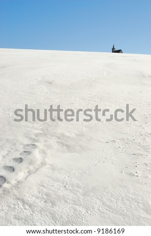 Church on the horizon of a snowy field