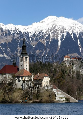 Church on the island of Lake BLED in SLOVENIA Europe and the snowy mountains in the background
