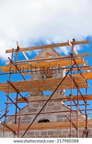 Church Restoration Scaffolding on Blue Sky Background - stock photo