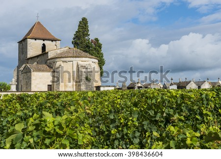 Church tower, graves and vinyard with grapes in the small city of Francs in France. - stock photo
