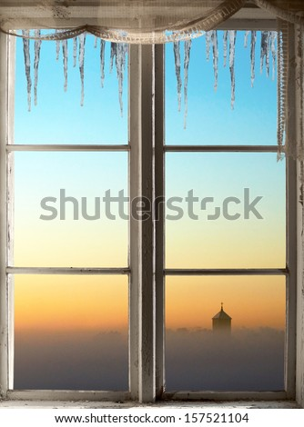 Church Tower On Foggy Winter Evening With Colorful Sky Viewed Through Old Window Icicles
