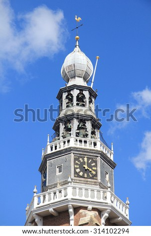 Church tower with a beautiful clock, and blue sky in the background