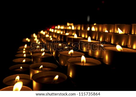 Church Votive Candles / A group of warm glowing candles on black background - stock photo