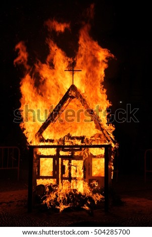 Church with cross burns in flames at dark night. It is a tradition in Spain at San Juan festival.