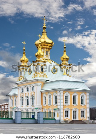 church with golden domes beside Grand Imperial Palace in Peterhof - stock photo