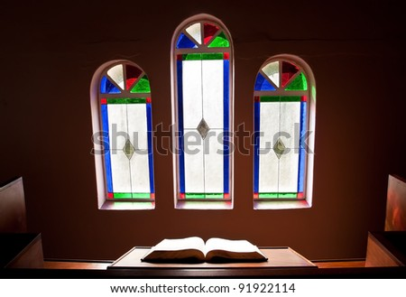 Church with lead glass windows with open Bible - stock photo