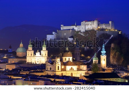 Churches and castle illuminated during night time in Salzburg old town, Austria - stock photo