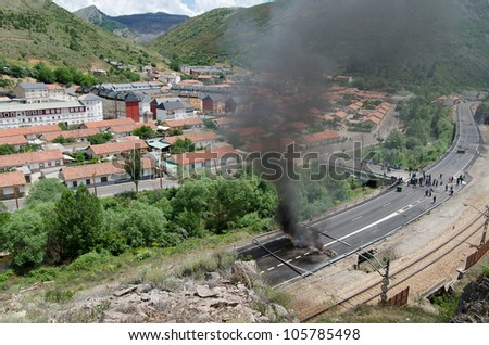 CIÑERA, SPAIN - JUNE 19: Striking miners barricade a national street and railway to protest against budget cuts in the coal industry and the shut down of the mines on June 19th 2012 in Ciñera, Spain.