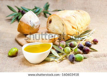 Ciabatta bread with olive oil and olive branch on burlap. - stock photo