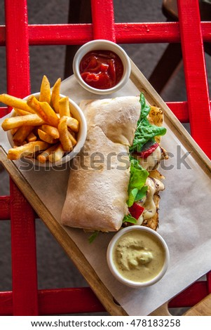 Ciabatta sandwich with bacon, arugula, tomato and cheese on wooden table. Fries and sauces.