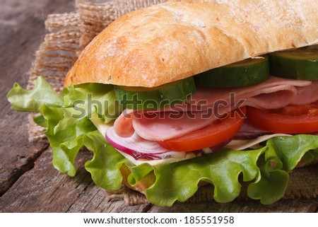 ciabatta sandwich with ham and vegetables macro on an old wooden table. horizontal.  - stock photo