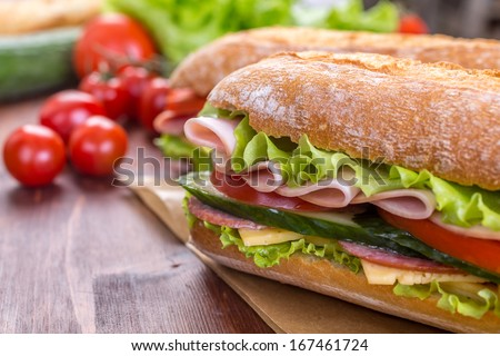 Ciabatta Sandwich with lettuce, slices of fresh tomatoes, cucumber, ham, salami and cheese - stock photo