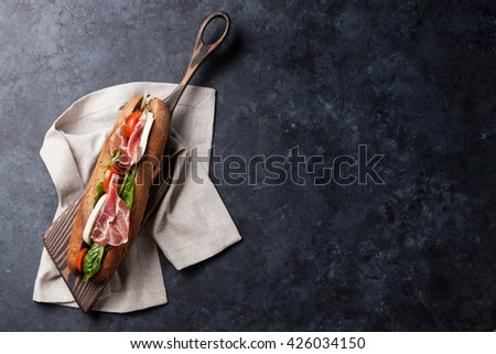 Ciabatta sandwich with romaine salad, prosciutto and mozzarella cheese on stone table. Top view with copy space - stock photo