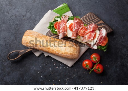 Ciabatta sandwich with romaine salad, prosciutto and mozzarella cheese over stone background. Sandwich cooking. Top view