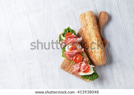 Ciabatta sandwich with romaine salad, prosciutto and mozzarella cheese over wooden background. Top view with copy space - stock photo