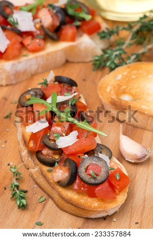ciabatta with tomatoes, olives, parmesan cheese and herbs, vertical, top view - stock photo