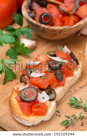 ciabatta with tomatoes, olives, parmesan on a wooden board, top view, vertical - stock photo