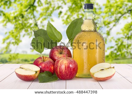 Cider and red apples with green leaves on a wood table in a sunny field