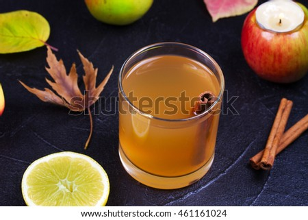 Cider glass with apples, lemon and cinnamon on black background