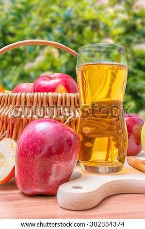 Cider - hot apple beverage on wooden table in garden. - stock photo