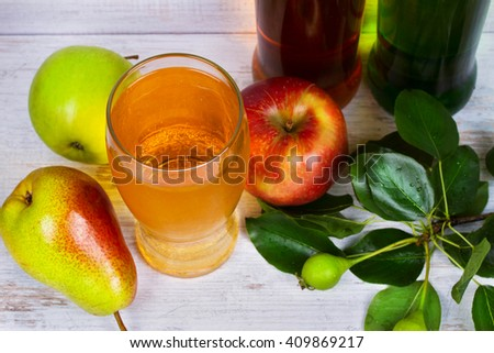 Cider with apples and pears on white wooden background. View from above