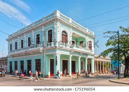 CIENFUEGOS, CUBA - MAY 5: Traditional colonial style colored buildings located on main street Paseo el Prado with local people walking around shown on 5 May 2008 in Cienfuegos, Cuba - stock photo
