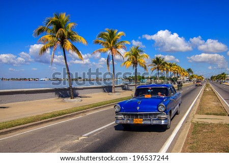 CIENFUEGOS - FEBRUARY 7: Classic taxi on the Malecon street on February 7, 2013 in Cienfuegos. These old and classic cars are an iconic sight of the Cuba island - stock photo