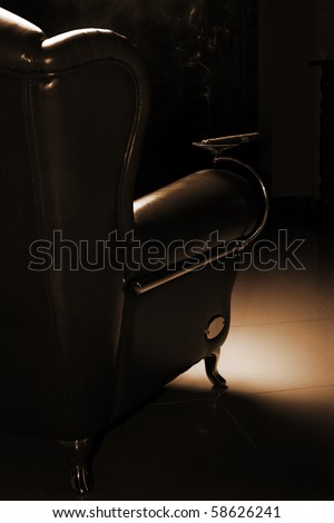 Cigar and beautiful leather armchair on marble to a floor - stock photo