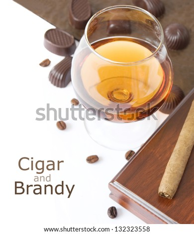 Cigar and brandy (cigar with cigar box, glass of brandy,candy and coffee beans isolated on white with sample text) - stock photo