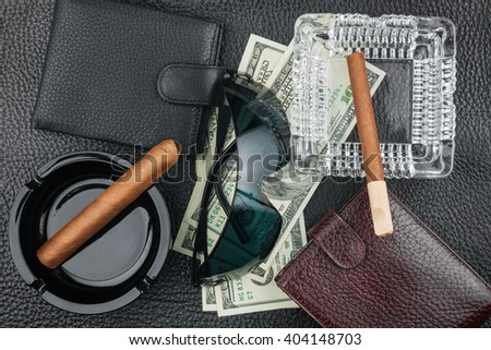 Cigar, ashtray, sunglasses, money, purse, on genuine leather, can be used as background