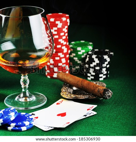 Cigar, chips for gamblings, drink and playing cards on green - stock photo