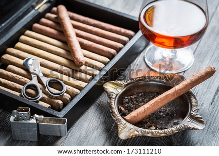 Cigar in ashtray, lighter and cognac - stock photo