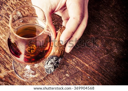 cigar in man hand with glass of alcohol. on the retro wooden table - stock photo